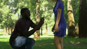 Afro-american man making proposal to girlfriend while they walking in park. Stock footage stock footage