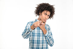 Afro american man pointing finger at camera. Portrait of a young afro american man pointing finger at camera isolated on a white background Stock Image