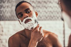 Afro-American Man Shaving in Bathroom at Morning. Young Afro American Man Shaving in Bathroom at Morning. Standing Man with Bare Torso in Bathroom. Personal Stock Photography