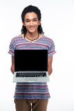 Afro american man showing blank laptop screen. Portrait of a happy afro american man showing blank laptop screen isolated on a white background Stock Image