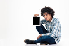 Afro american man showing blank tablet computer screen. Smiling afro american man sitting on the floor and showing blank tablet computer screen isolated on a Royalty Free Stock Photography