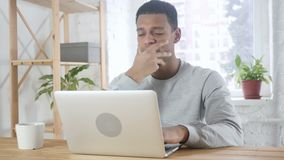 Afro-american man sitting in office upset by loss, working on laptop stock video footage
