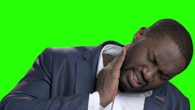 Afro-American man with strong neck pain. Unhappy dark-skinned man in formal wear suffering from neck ache on green screen. Pinched nerve concept. What causes stock footage