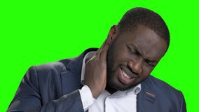 Afro american man suffering from neck ache. Stressed dark-skinned businessman has terrible pain in his neck on chroma key background close up. Causes of neck stock video