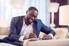 Afro American man taking notes. Lets work. Satisfied young afro American man in suit while taking notes in a diary while sitting on the sofa in a hotel Royalty Free Stock Image