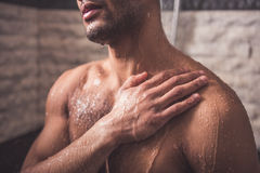 Afro American man taking shower. Handsome naked Afro American man is taking shower in bathroom Stock Images