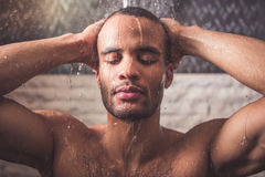 Afro American man taking shower. Handsome naked Afro American man is taking shower in bathroom Stock Photography