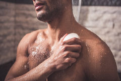 Afro American man taking shower. Handsome naked Afro American man is using a soap while taking shower in bathroom Stock Photo
