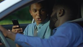 Afro-american man trying to glance in sons smartphone disturbing privacy, secret