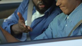 Afro-american man unhappy with teenager scrolling smartphone on driver seat stock video footage