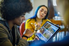 Afro american man using tablet looking for photos.Group of multiethnic people having business team meeting in restaurant royalty free stock photo