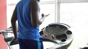 Afro-American man walking on treadmill and checking his smartphone in the gym. Stock footage stock video