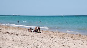 Afro-American mane in bathing suit laying on sand near the oceal looking at his smartphone royalty free stock image