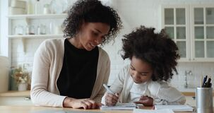 Afro american mom helping cute school child daughter checking homework