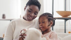 Afro american mother with little daughter girl sitting on sofa at home talking holding teddy bear. Single parent ethnic