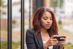 Afro-American Office Woman Texting on her Phone Stock Images