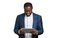 Afro american office worker with computer tablet. Smiling black businessman with digital tablet on white background. Manager working on pc device Stock Images