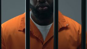 Afro-American prisoner in handcuffs feeling sorrow about made crime, guilty. Stock footage stock footage