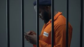 Afro-american prisoner using phone in cell, corruption in prisons, prohibition. Stock footage stock video footage