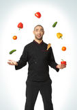 Afro American professional cook juggling vegetables. stock photos