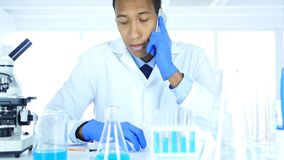 Afro-American Scientist Talking on Phone in Laboratory Royalty Free Stock Photo