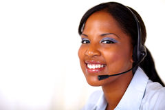 Afro-american secretary smilig at you. Afro-american secretary smiling at you with headphones - copyspace Royalty Free Stock Photos