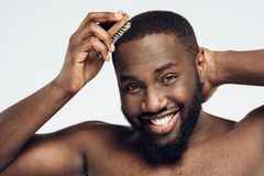 Afro American smiling man combs hair. royalty free stock photo