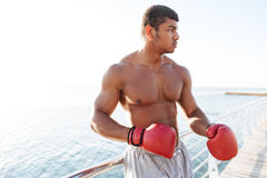 Afro american sportsman in red gloves doing exercises outdoors Royalty Free Stock Images