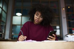 Afro american student sitting at table in university campus looking into camera holding modern smartphone Royalty Free Stock Photo