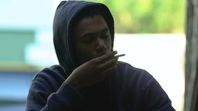 Afro-American teen boy trying cigarette, coughing after smoking, bad habit