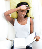 Afro-american teenager feeling sick holding a book. Lying on a sofa Stock Photo