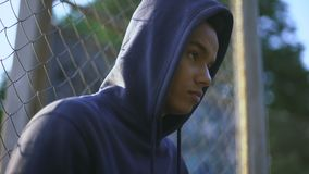 Afro-american teenager holding baseball bat, youth gang in ghetto, closeup. Stock footage stock video