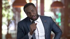 Afro-american tv presenter on blurred background. Attractive dark-skinned entertainer talking into microphone. People, media, entertaining stock video