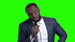 Afro-american tv presenter on green screen. Attractive dark-skinned entertainer talking into microphone on Alpha Channel background stock video footage