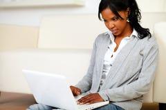 Afro-american ung kvinnlig som använder henne bärbar dator Fotografering för Bildbyråer