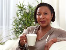 Afro american woman. African-american woman drinking tea at cozy apartment relaxing Stock Photo