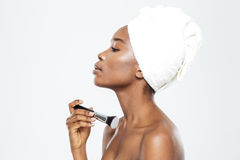 Afro american woman applying makeup with brush Stock Photo