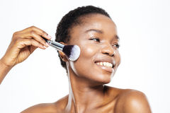 Afro american woman applying makeup with brush Stock Images