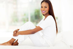 Afro american woman bed. Happy afro american woman sitting on bed at home Royalty Free Stock Images
