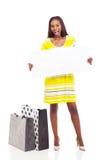 Afro american woman blank billboard. Excited afro american woman with shopping bags holding blank billboard stock photo