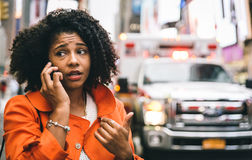 Afro american woman calling 911 in New york city. Royalty Free Stock Images