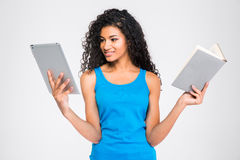 Afro american woman choosing between tablet computer or paper book Stock Images