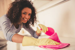 Afro American woman cleaning. Beautiful young Afro American woman is looking at camera and smiling while cleaning kitchen Stock Photography