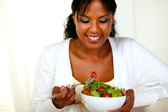 Afro-american woman eating fresh vegetable salad. Portrait of an afro-American young woman eating fresh vegetable salad at soft colors composition Stock Photos