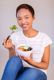 Afro american woman eating. Happy afro american woman eating green salad at home Stock Photography