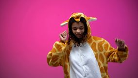Afro-American woman in funny giraffe pajamas dancing isolated on pink background. Stock photo royalty free stock photography