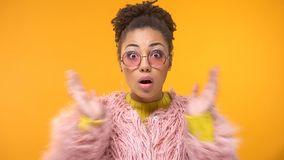 Afro-American woman in funny pink coat surprised by interesting news, gossip stock photography