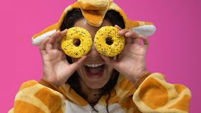 Afro-American woman in giraffe pajamas closing eyes with donuts, fooling around. Stock footage stock footage