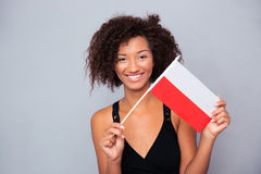 Afro american woman holding Poland flag. Portrait of a happy afro american woman holding Poland flag over gray background and looking at camera Royalty Free Stock Images