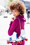Afro-American woman holding roller-skates Stock Photos
